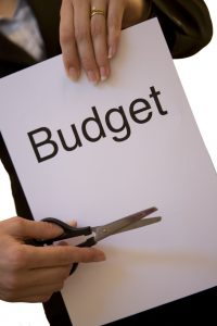 woman holding a budget sign and scissors
