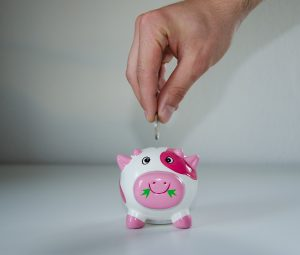 dropping a coin in a piggy bank